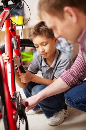 bike tire: Portrait of little boy and his father repairing bicycle in garage Stock Photo