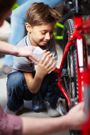 Portrait of cute boy lubricating bicycle chain in garage photo