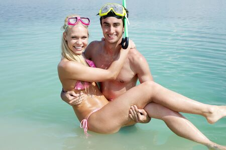 scuba goggles: Portrait of happy guy holding his girlfriend while standing in water  Stock Photo