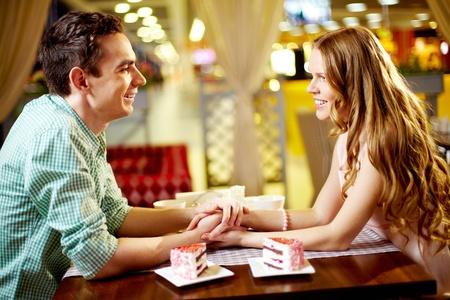 cena romantica: Una giovane coppia felice seduto nel ristorante e guardando l'un l'altro