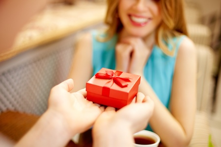 Close-up of man giving red giftbox to happy girl photo