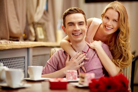 man woman hugging: A young happy couple looking at camera in cafe