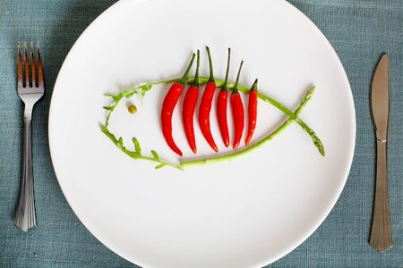 edible fish: Image of plate with hot chili peppers and asparagus in form of fish