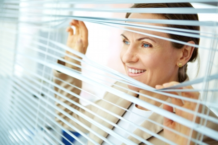 Smiling business woman looking out of the window with blinds photo