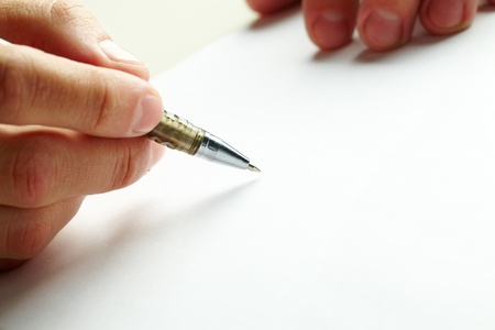 ball pen: Close-up of human hand holding metallic pen over blank paper