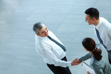 Image of business partners handshaking after signing contract photo