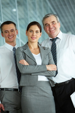 A business team with pretty leader in front looking at camera and smiling  photo