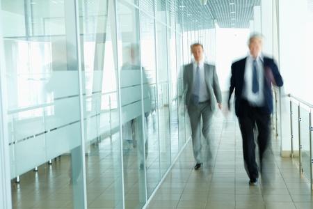 corridoi: Uomini d'affari a piedi nel corridoio dell'ufficio Archivio Fotografico