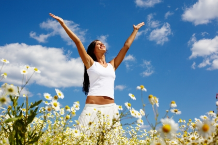 emotional freedom: Young woman holding hands high up while enjoying the warm sunny day Stock Photo