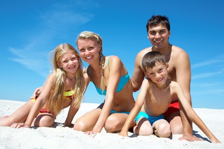 sibling: Photo of happy family sitting on sand on summer vacation