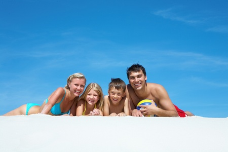 Photo of happy family relaxing on sand photo