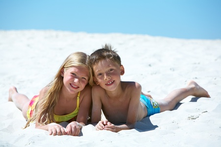 Photo of happy siblings lying on sand on summer vacation Stock Photo