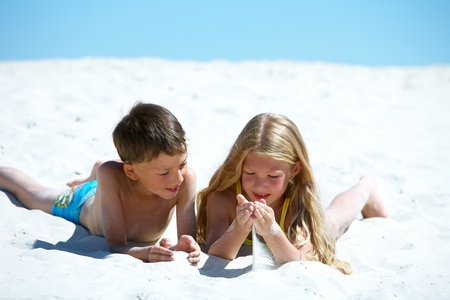 Photo of happy siblings lying on sandy beach photo