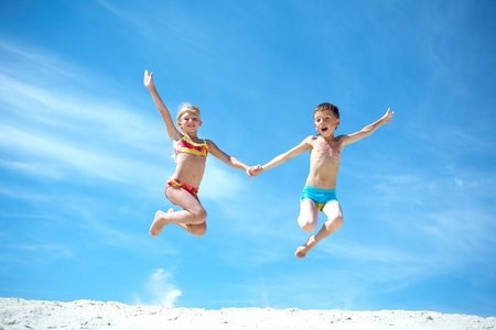 Photo of happy siblings jumping over sand and looking at camera photo