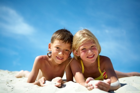 Photo of happy siblings lying on sand and looking at camera photo