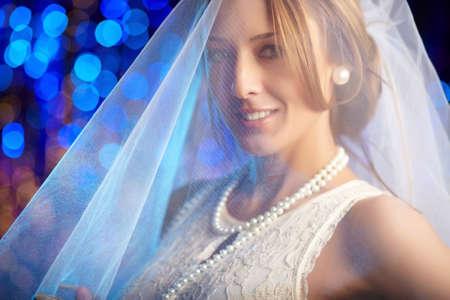 bridal veil: Portrait of a smiling bride in white veil