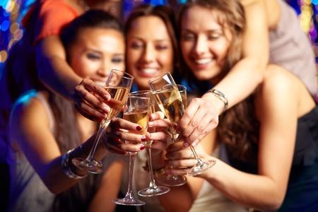 clinking: Grupo de chicas de fiesta haciendo sonar las flautas con vino espumoso