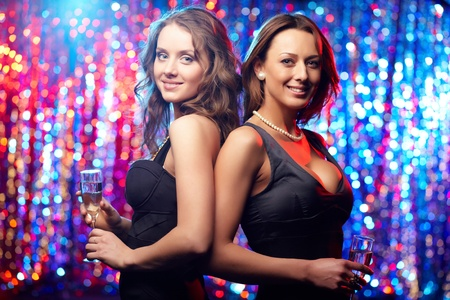 Two sensual women dressed in black posing against sparkling background photo