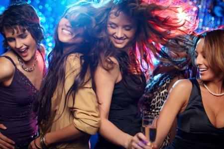 楽しいを持っている若い女性のナイトクラブでダンス