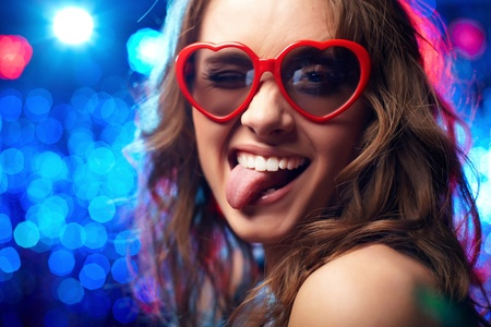 Portrait of a girl wearing heart-shaped glasses playfully showing her tongue