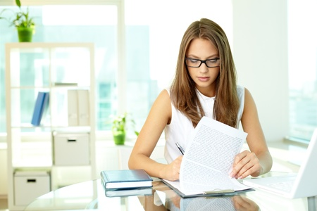 concentrated: Concentrated girl working with document attached to a clipboard Stock Photo