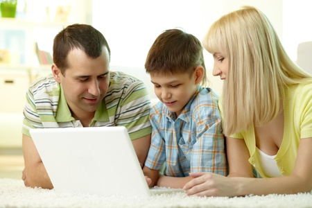 Cheerful family of three using laptop together photo