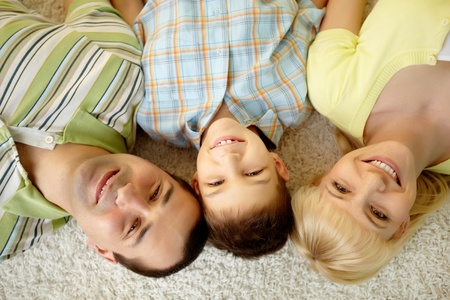 Overview of a happy family lying on the carpet photo