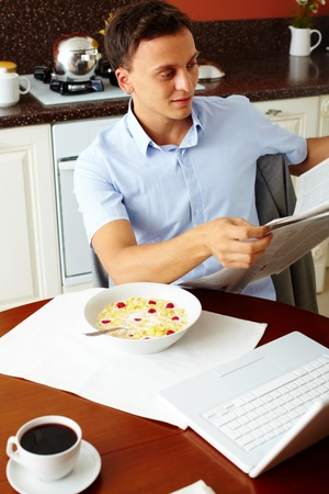 Vertical shot of a man reading morning newspaper at breakfast Stock Photo - 13313498