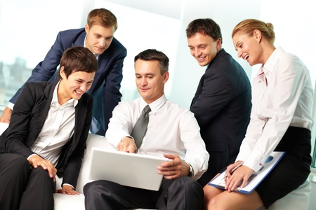 Leader of business team pointing at the screen of his laptop, his colleagues looking and laughing photo