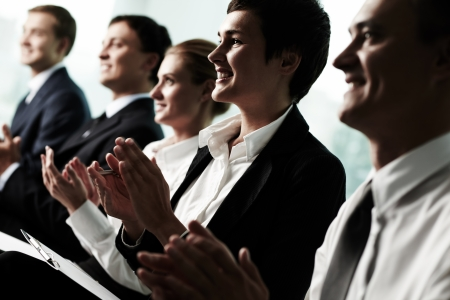 congratulate: Tilt up of roup of business people applauding to a successful speaker  Stock Photo