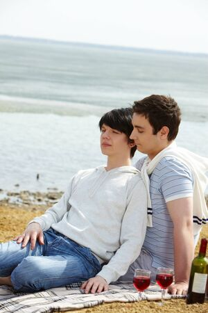couple resting at beach, boy leaning against his friend photo