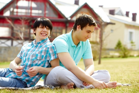 homosexuales: Los gays jóvenes sentados juntos en el césped disfrutando de un clima cálido