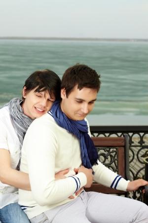 amigos abrazandose: Hombre alegre joven abrazando a su amante sonriendo dreamingly Foto de archivo