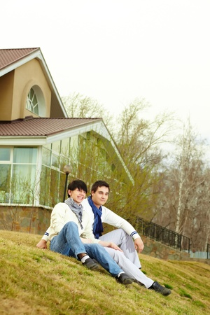 Tilt up of stylish homosexual lovers sitting on the grass in front of the townhouse photo