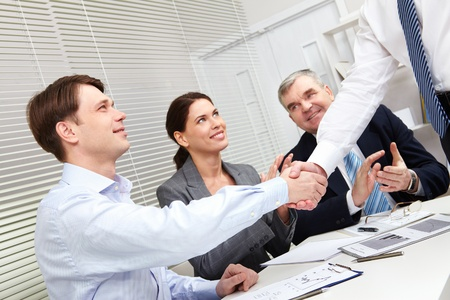 conclude: Tilt-up of business people giving a handshake to conclude the deal