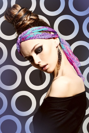 Fashionable portrait of a charming girl wearing a bright headscarf, professional makeup and hairdo photo