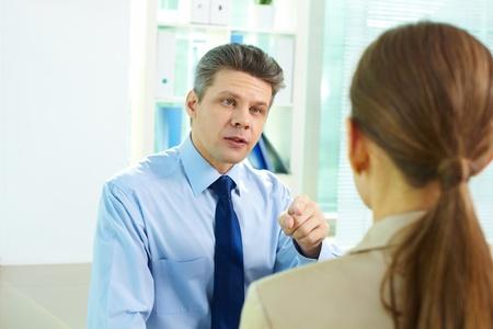 jefe enojado: Hombre de negocios apuntando a su socio femenino como si acusándola