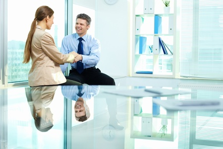 Smiling businessman holding affectionately his female colleague's hand as a sign of trust and support photo