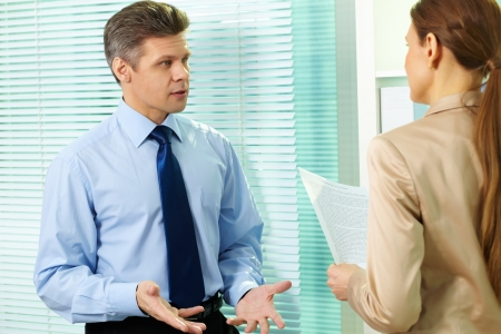 annoyed: Mature businessman picking a bone with his female co-worker Stock Photo