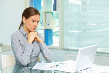 Elegant business woman looking pensively at the screen of her laptop Stock Photo - 13408585
