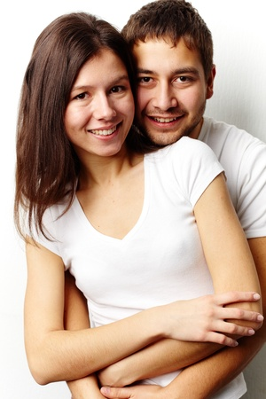 couple cuddling: Vertical portrait of a flirting couple isolated against white background