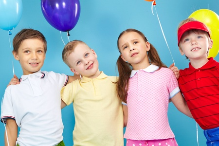 kids hugging: Portrait of kids holding colorful balloons Stock Photo