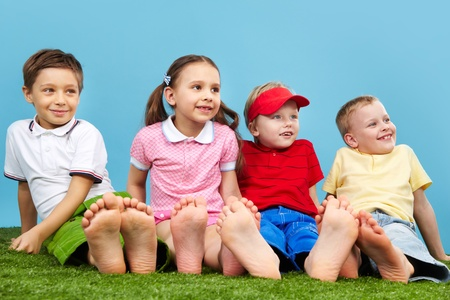 Happy children sitting on the grass barefoot Stock Photo - 13408628