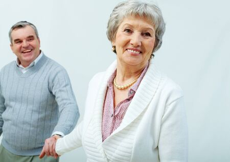 Cheerful seniors holding hands romantically photo