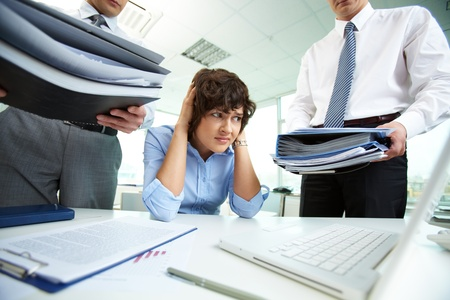confused person: Terrified secretary touching her head while looking at big heaps of papers Stock Photo