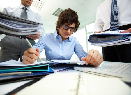 Terrified accountant doing financial reports being surrounded by businessmen with huge piles of documents photo