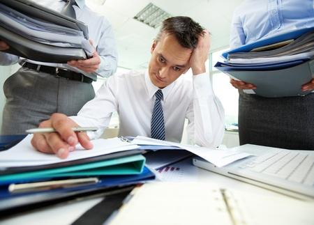 in a pile: Perplejo contador haciendo los informes financieros de estar rodeado de socios de negocios con enormes pilas de documentos Foto de archivo