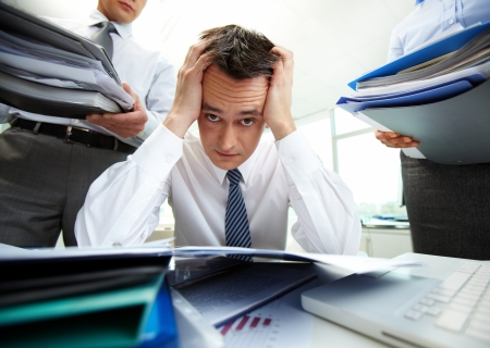 troubles: Perplexed accountant touching his head being surrounded by business partners with huge piles of documents