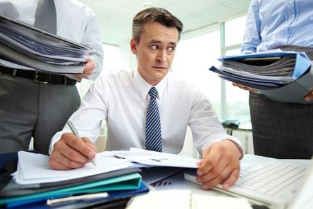 persona confundida: Contador de shock mirando a enormes pilas de documentos mientras que hace los informes financieros