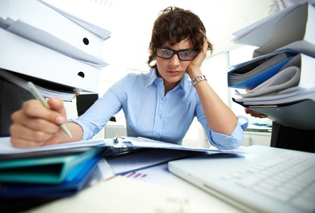 perplexed: Perplexed accountant doing financial reports being surrounded by huge piles of documents Stock Photo